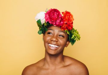 Confidence, a young woman with a headband made of flowers smiles and looks happy