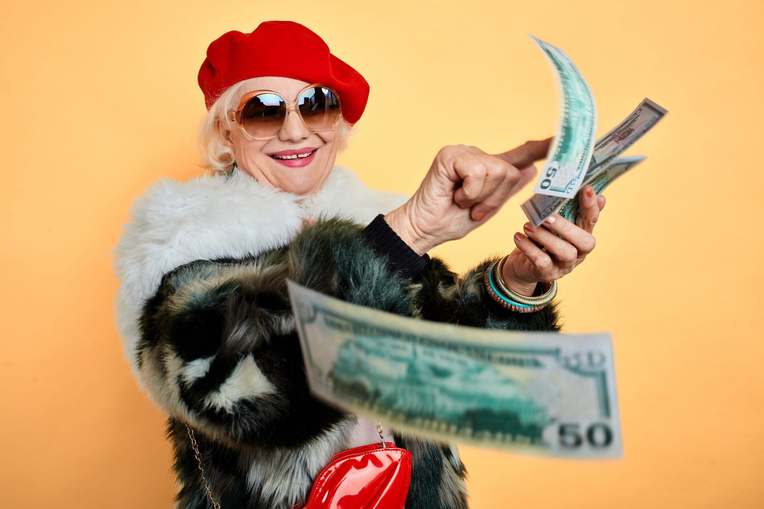 Older Lady with large sunglasses gleefully counting dollar bills